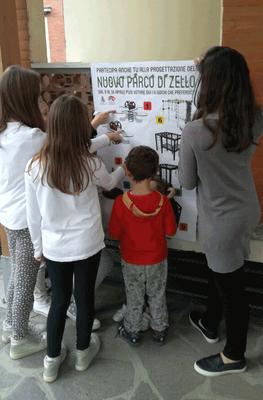 I bimbi di fronte al manifesto per scegliere i giochi del nuovo parco di Zello